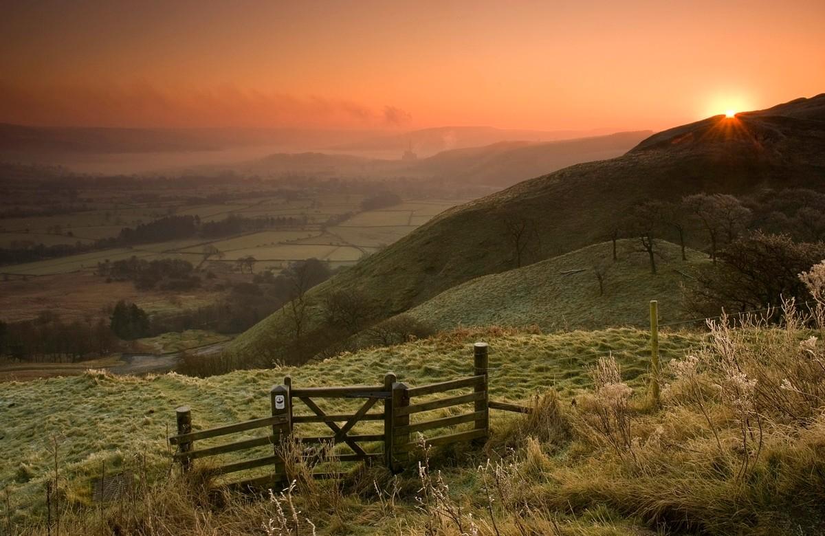 Early morning sun rising over Treak Cliff from Little mam Tor, Peak District