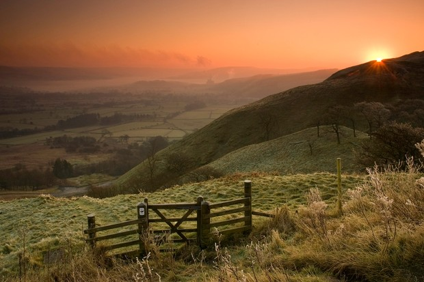 Early morning sun rising over Treak Cliff from Little mam Tor, Peak District