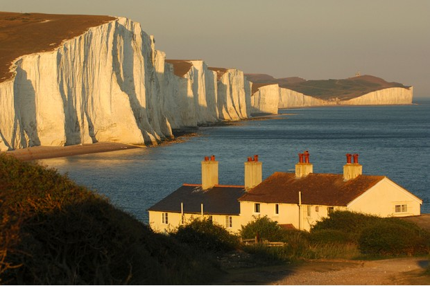"The golden light of dusk illuminates (and cast shadows over) the famous English view of coastguards cottages set against the English Channel and ""Seven Sisters"" chalk cliffs"