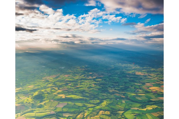 Rays of sunlight illuminating the picturesque patchwork quilt landscape of green fields, farms and misty mountains under panoramic skies from high above. ProPhoto RGB profile for maximum color fidelity and gamut.