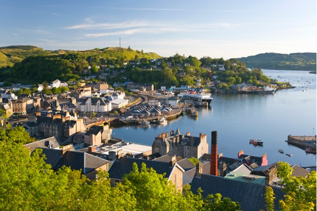 View over the harbour from McCaig's Tower, distillery chimney prominent, Oban, Argyll and Bute, Scotland, United Kingdom, Europe.