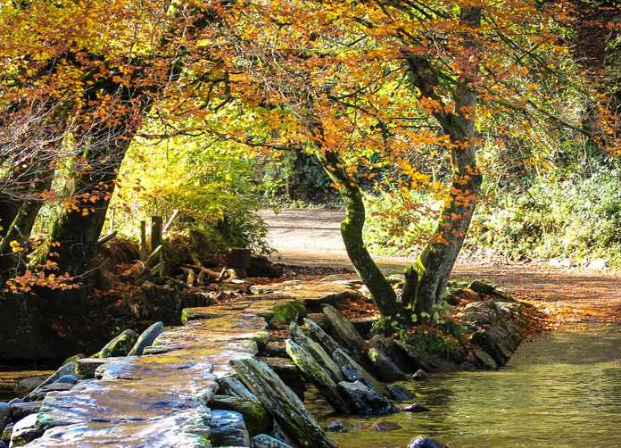 Photo of Tarr Steps a Clapper bridge across the River Barle in the Exmoor National Park, Somerset, England.