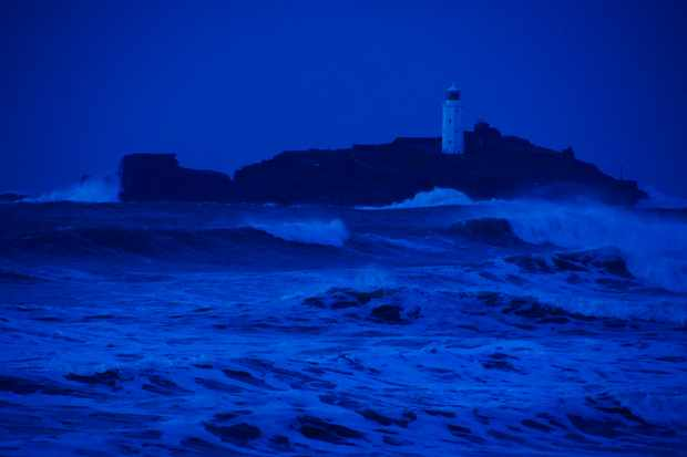 St Ives Bay during the storms which beset the British Isles in January and February 2014. Godrevy Island and it's lighthouse are visible amid the rough seas of an incoming tide in the background in Cornwall, England, UK.