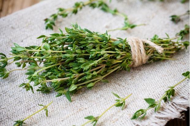 bundle of raw fresh organic thyme on sackcloth