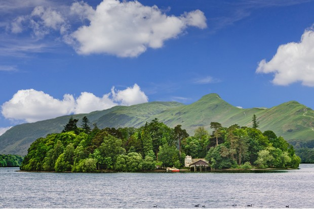Derwent Water and Mountains, Keswick, Lake District, England. The Lake District, also known as The Lakes or Lakeland, is a mountainous region in North West England. A popular holiday destination, it is famous for its lakes, forests and mountains (or fells) and its associations with the early 19th century writings of William Wordsworth and the other Lake Poets. Ducks swimming in the lake are in the image. Blue sky with clouds is in background. HDR photorealistic image.