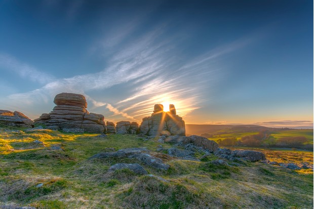Hound Tor at sunset with the sun shining between the rocks on Dartmoor in Devon
