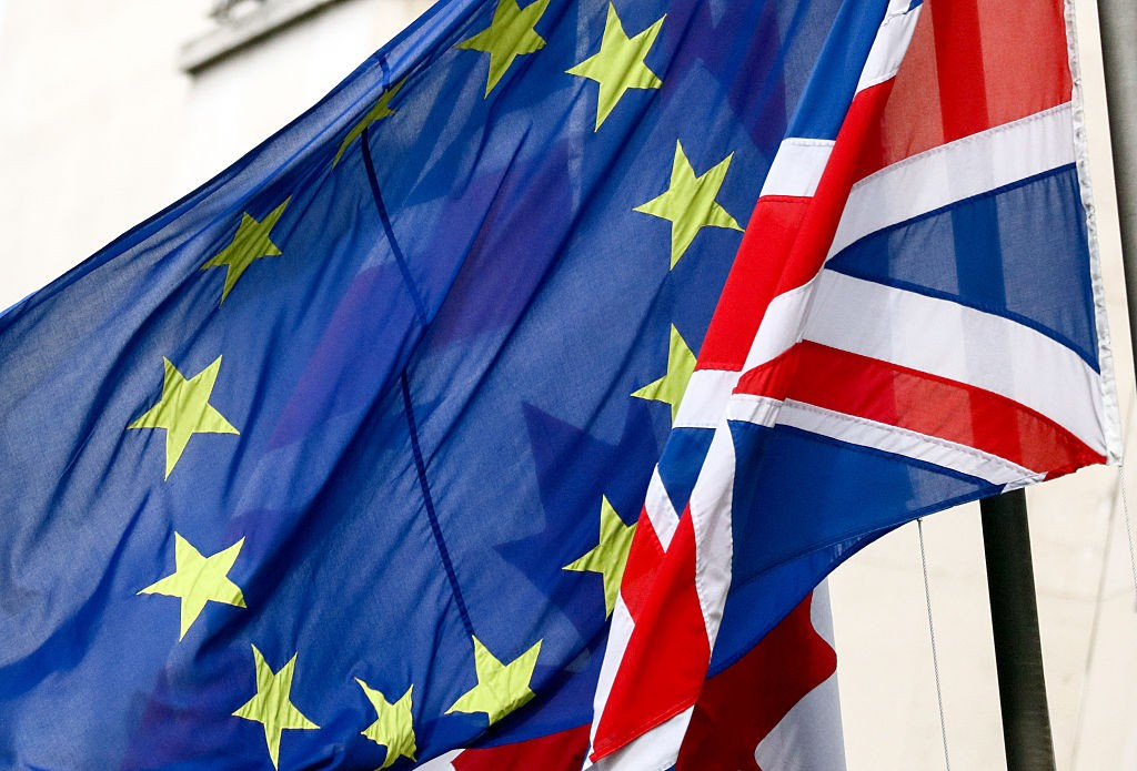 A British Union flag, commonly known as a Union Jack, right, flies next to a European Union (EU) flag, in London, U.K., on Wednesday, Feb. 17, 2016. German Chancellor Angela Merkel threw her political muscle behind the push for a deal to keep the U.K. in the European Union as diplomats worked to bridge the remaining differences between its members.Photographer: Chris Ratcliffe/Bloomberg via Getty Images