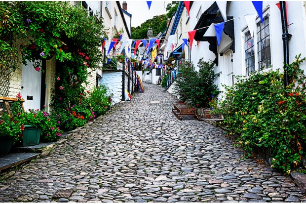 Cobbled street in Clovelly, North Devon, England. Picturesque English seaside town, early morning.