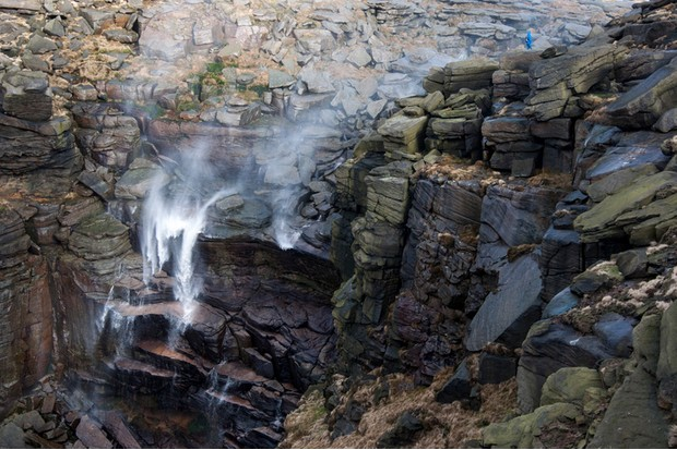 Waterfall on Kinder Scout in the Peak District. A windy day with the water blown back upwards. A lone figure in blue clothing stands on the edge of the rocky scene.