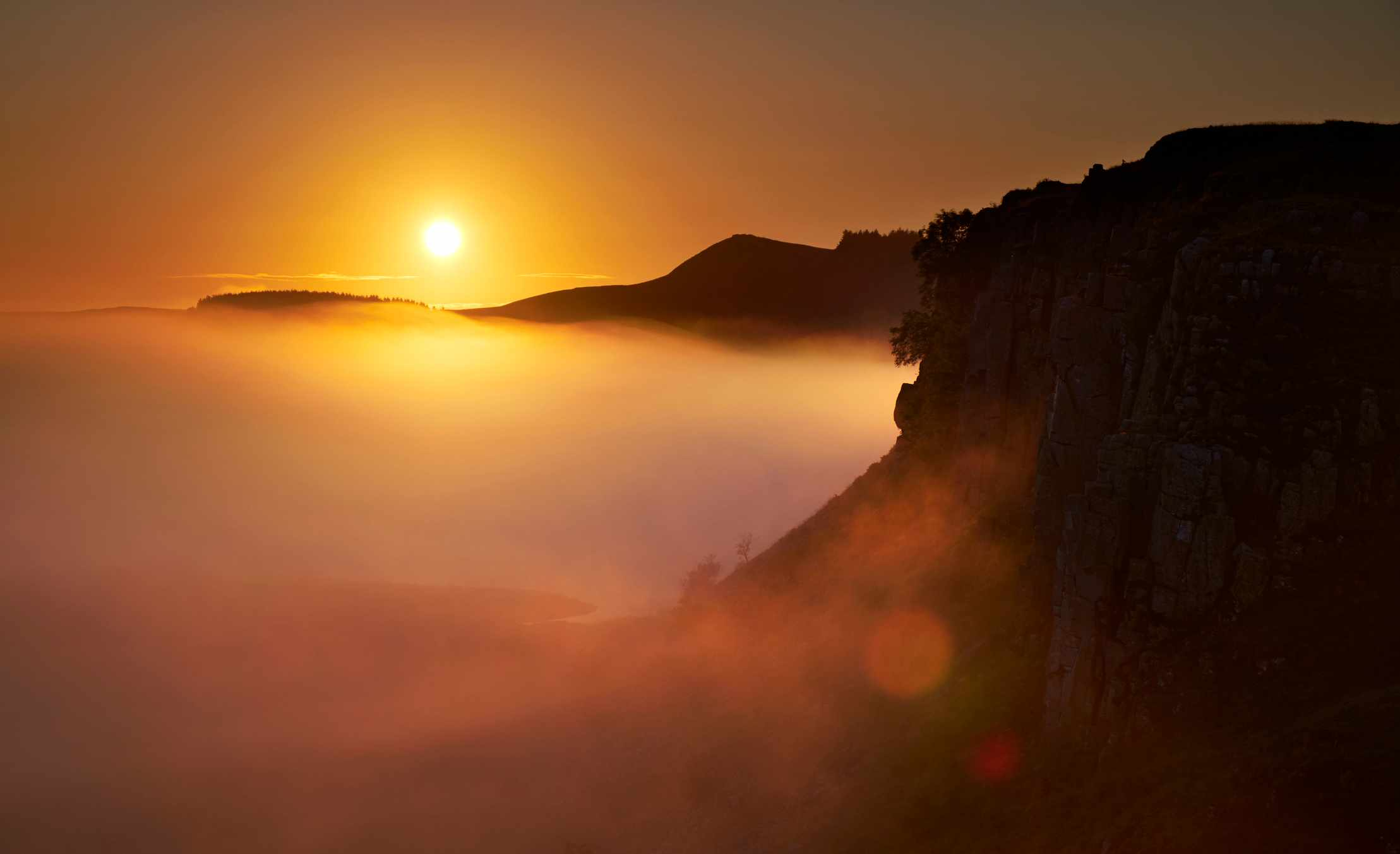 Dawn breaks over the still, misty waters of Crag Lough and Hadrian's Wall in Northumberland, at the very north of England. The ancient Roman fortified wall runs between England and the wild lands to the north, though much of the scenery at this early hour is shrouded in mist.