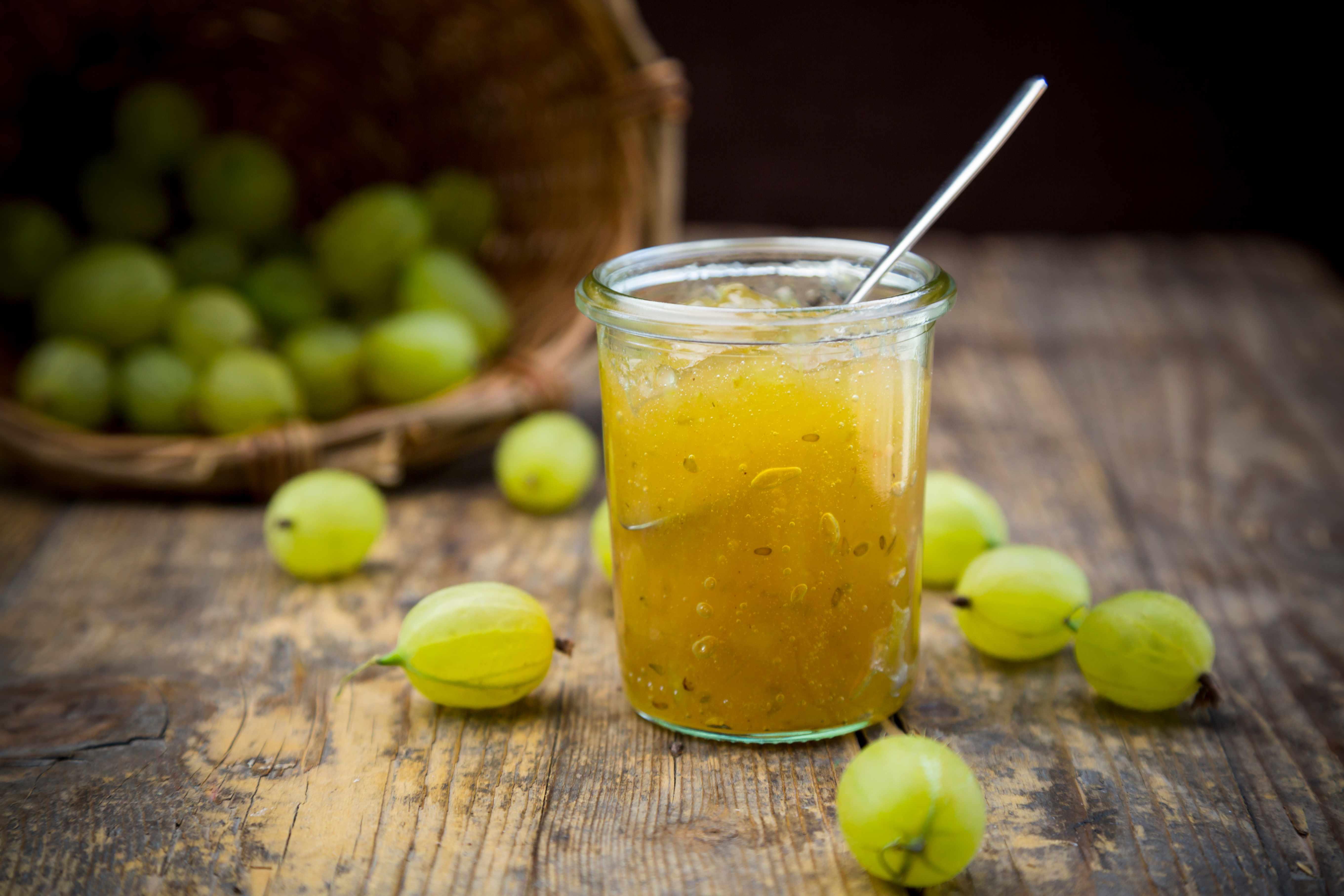 Jar of gooseberry jam, basket and organic gooseberries on dark wood