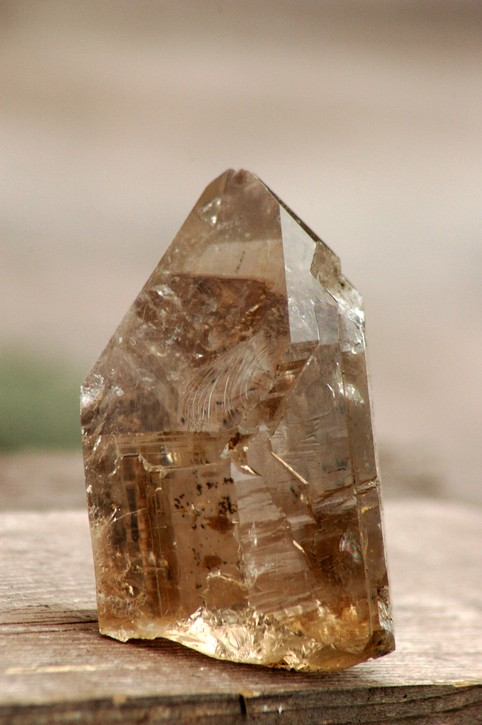 Rough natural smokey quartz crystal with dark inclusions