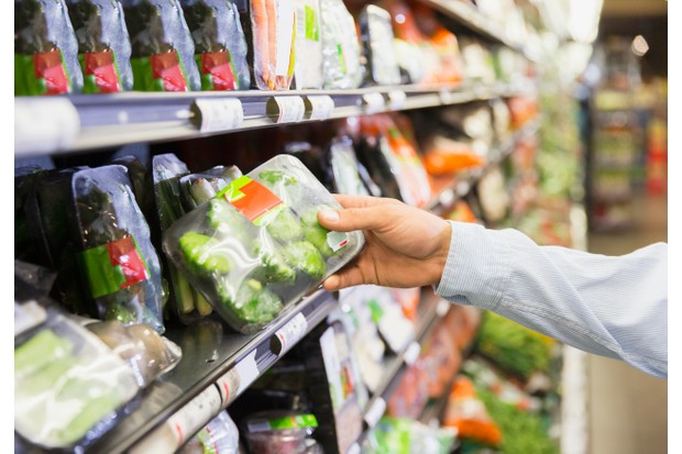 Close up of man holding produce in grocery store