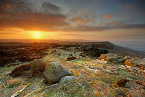 Wide angle view of the sun rising over Curbar Edge in the Peak District National Park, Derbyshire, England, UK.