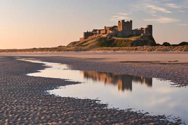 Bamburgh Castle and reflection in Bamburgh Beach tidal pools, Northumberland, England, United Kingdom, Europe