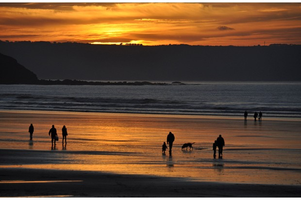 Families and dogs walking on the beach at sunset, Westward ho, North Devon, England