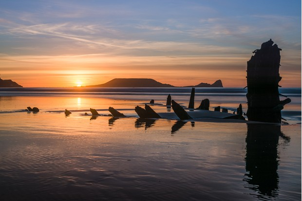 The remains of the Norwegian barque Helvetia and Worm's Head are probably the most photographed points of interest on the whole Gower Peninsula, South Wales. They can be found in Rhossili Bay, and can both be seen in this photography.