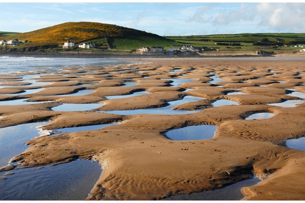 A receding tide at Croyde Bay leaves pools of sea water behind on a Devon, UK, beach during high summer.