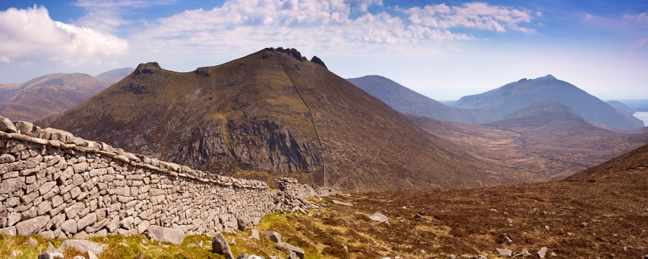 The Mourne Wall and the peak of Slieve Binnian in the Mourne Mountains in Northern Ireland on a sunny day.