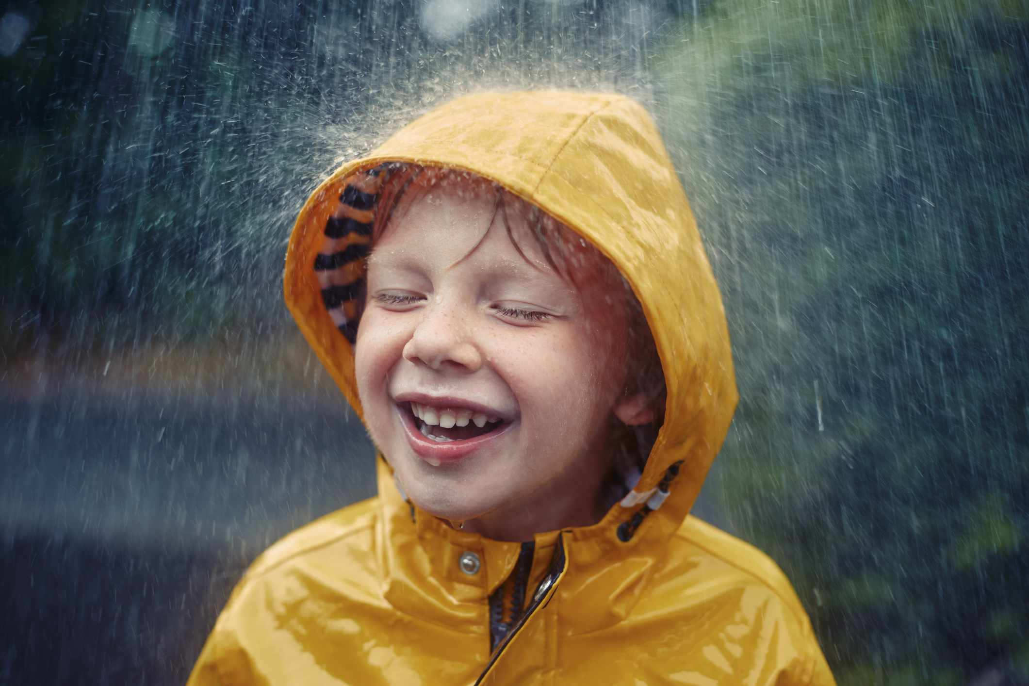 Happy smiling little boy out in the rain
