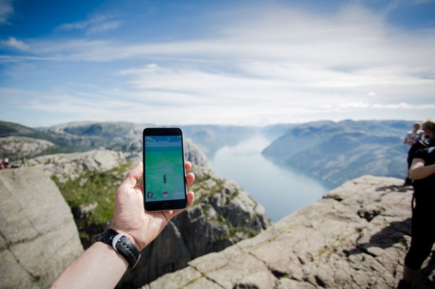 Hand holding mobile phone above a mountain range
