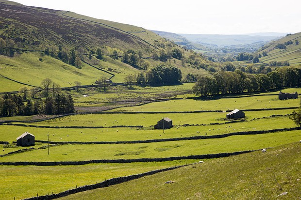 Stone barns and fields in Littondale, Yorkshire Dales national park, England, UK. (Photo by: Geography Photos/UIG via Getty Images)