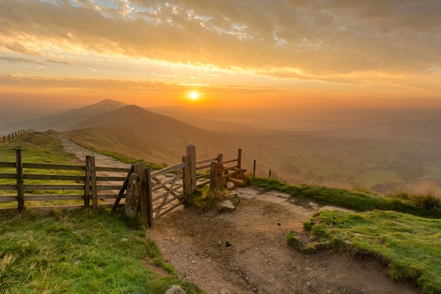 Golden sunrise at Mam Tor in the English Peak District on a hazy Autumn Morning with wooden gate.