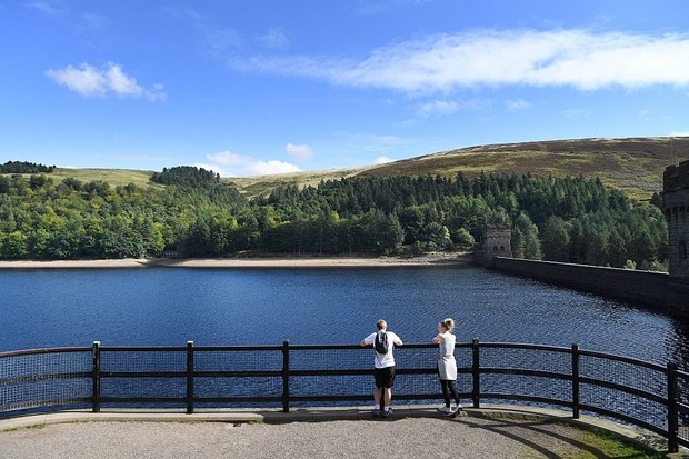 Visitors look out towards Derwent Dam at Derwent Reservoir in Derbyshire