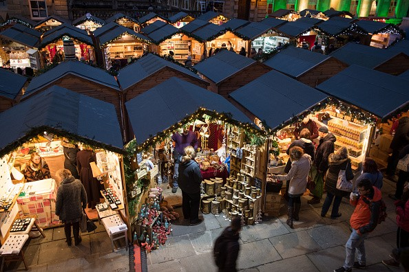 BATH, ENGLAND - NOVEMBER 24: Christmas shoppers browse stalls at the traditional Christmas market that has opened close to the historic Roman Baths and Bath Abbey on November 24, 2016 in Bath, England. Originating in Germany, Christmas markets have become increasingly popular in British towns and cities in recent years as a way of boosting festive sales and visitor numbers. (Photo by Matt Cardy/Getty Images)