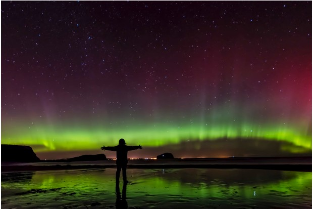 Female in awe of the Aurora, Northern Lights, Seacliff Beach with Bass Rock in the middle distance, East Lothian, Scotland.