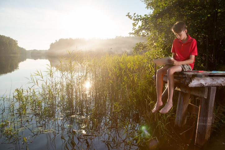 Teenager boy sitting on a wooden pier by forest lake drawing with pastel sticks in an evening light