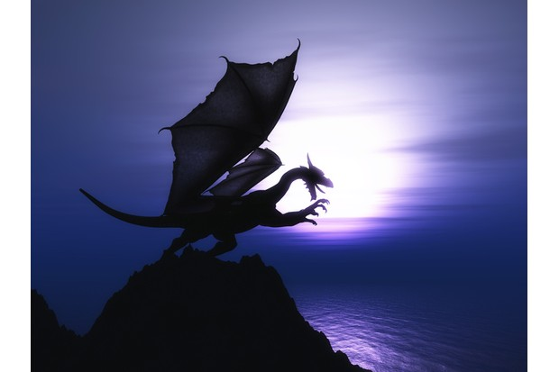 3D render of a fantasy dragon on a cliff against a sunset ocean