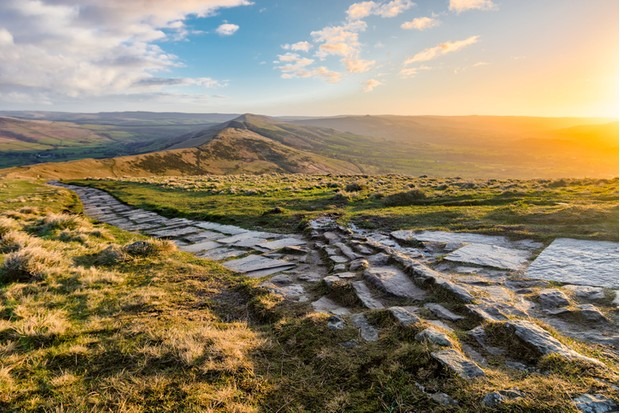 Rural stone footpath on the edge of Mam Tor in the Peak District at sunrise.