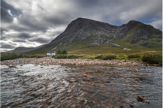 The remote Lagangarbh Hut along River Coupall in front of Buachaille Etive Mor in Glen Coe on a rainy day, Scottish Highlands, Scotland