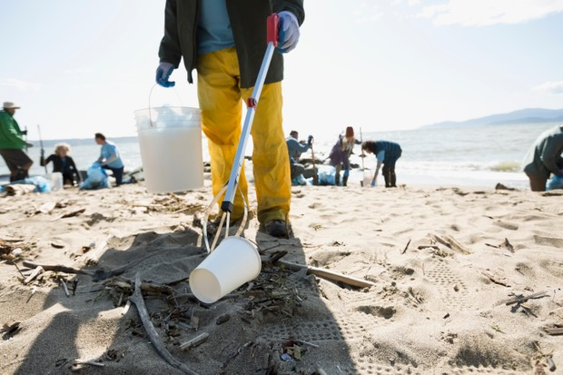 Beach cleanup volunteer using claw to pick up litter on beach