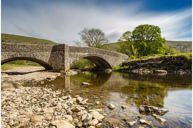 The bridge over the river at Buckden, North Yorkshire in the Yorkshire Dales. Long exposure shot to give some cloud blur, and reflections in the water.