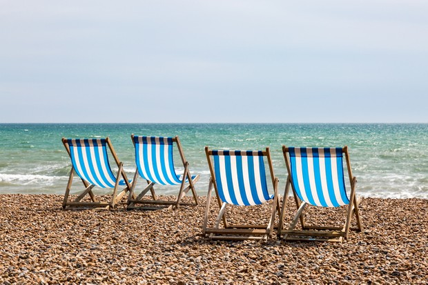 A photograph of four empty deck chairs on the beach at Brighton, UK.