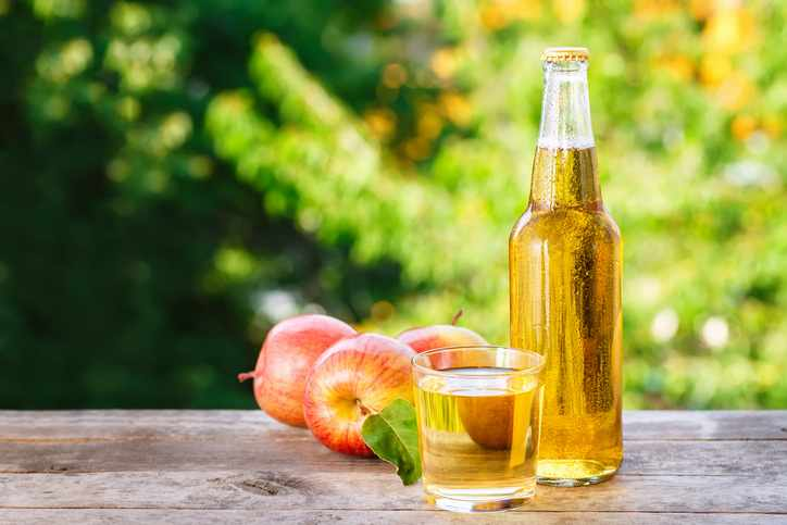 apple cider in glass and bottle  on wooden table on blurred natural background. Refreshing summer drink