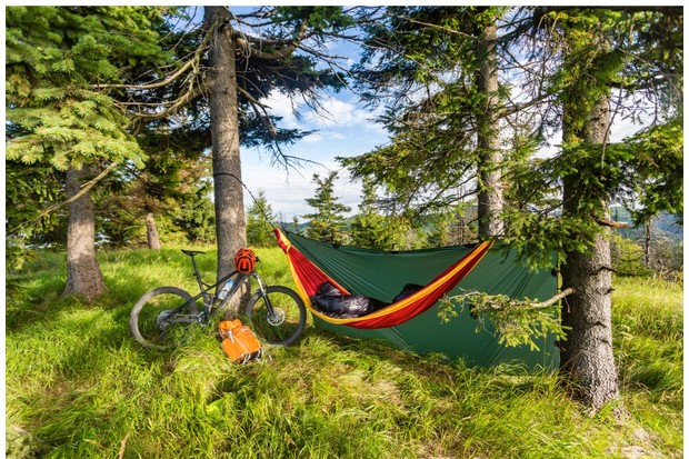 Camping in woods with hammock and sleeping bag on mountain biking adventure trip in green mountains. Travel campsite when mtb cycling with backpack. Lightweight shelter in wilderness forest, Poland.
