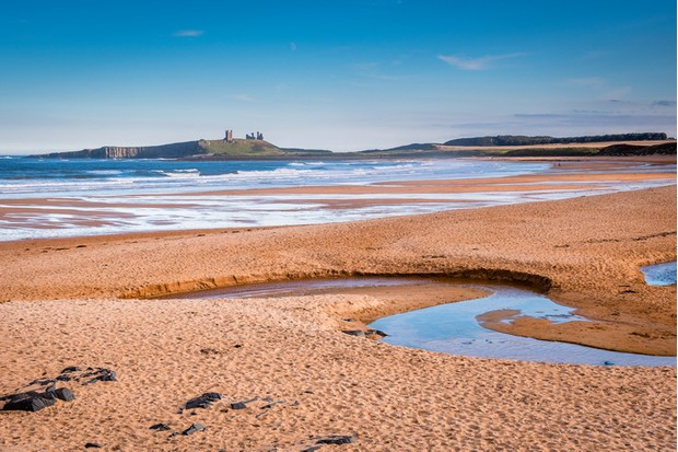 Embleton Bay is a wide sandy beach with the ruins of Dunstanburgh Castle providing a stunning backdrop,located on the Northumberland coastline with Embleton Burn in the foreground