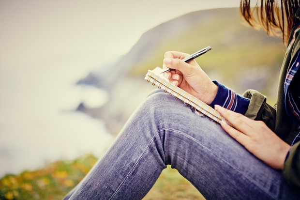 Young woman writing in diary while sitting on mountain