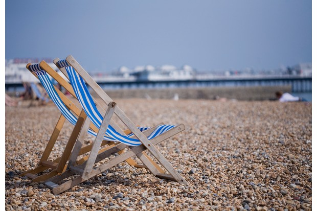 Two blue and white deckchairs on Brighton pebble beach, UK