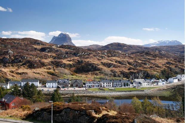 Scottish village of Lochinver on a sunny spring day with Suilven behind