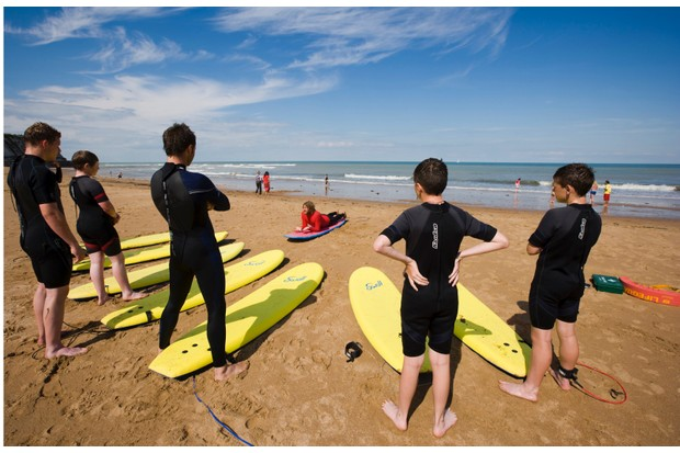 A group of people learning how to manoeuvre on a surf board on the beach at Joss Bay on the Isle of Thanet in Kent.