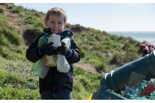 Young boy helping to litter pick on a beach