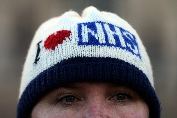 LONDON, UNITED KINGDOM - JANUARY 12:  A woman wears an 'I love NHS' woolie hat as she joins members of staff taking part in a picket outside St Thomas' Hospital on January 12, 2016 in London, United Kingdom. Junior doctors in England have gone on strike in a dispute with the government over a new contract. The doctors are only providing emergency cover during the 24-hour walkout, which started at 8:00am with the NHS so far postponing 4,000 routine treatments.  (Photo by Carl Court/Getty Images)