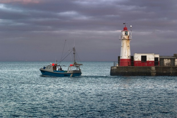 A small fishing vessel chugs out of port at Newlyn