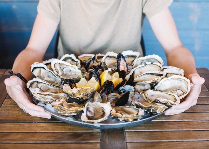 Man's hands holding a seafood platter with oysters, clams and mussels.