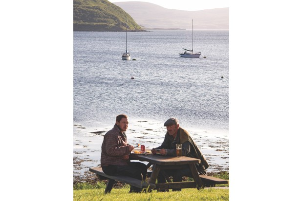 BC2A3R Two men drinking at a picnic table, Stein, Isle of Skye, Inner Hebrides, West Coast of Scotland, UK. Image shot 2009. Exact date unknown.