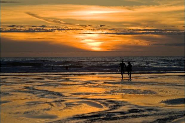 Surfers enjoying the sunset at Perranporth